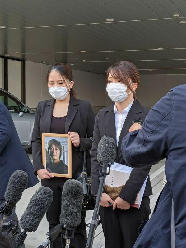 刑事裁判のあと、亡き父の遺影を手に各メディアの質問に答える長女の杏梨さん(左)と次女(筆者撮影)