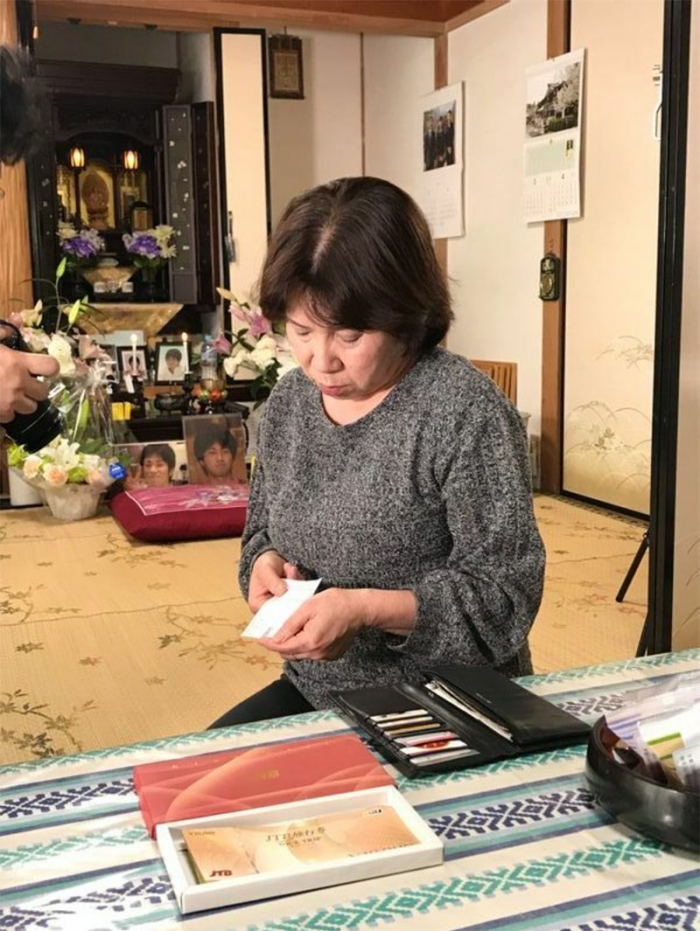 隆史さんが亡くなる1週間前、父親の還暦祝いに贈ってきた旅行券を見つめる母親のるり子さん。遺品の財布には、2日前に東京から発送した際の書留の控えもそのまま残されていた(筆者撮影)
