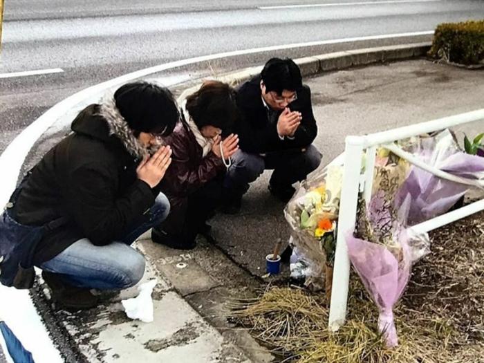 ひき逃げ事件発生現場で手を合わせる隆史さんの両親と兄(遺族提供)