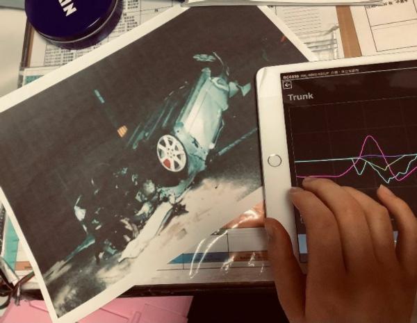 事故直後の事故車の写真を見る陽子さん。加害者が運転する車は時速150キロを超すスピードで制御不能に陥り、衝突の末、転覆した状態で停止した(石田さん提供)