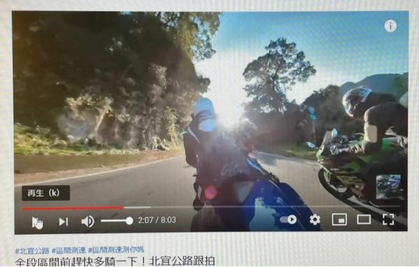 上の動画の中の一コマ。左のライダーが、今回の事故で死亡した本人。このカットの3秒後に通過する場所が、今回の事故現場となった(YouTube画面を筆者撮影)
