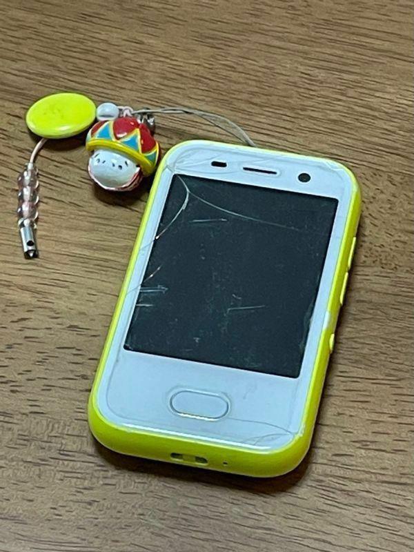 耀子さんが持っていたキッズ携帯。ストラップにはパパからもらった沖縄土産がつけられている(筆者撮影)