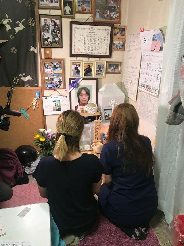 2年前の事故で亡くなった仲澤勝美さんの遺影に語り掛ける妻と長女(筆者撮影)