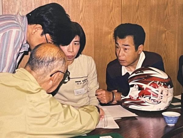 2001年、事故から約半年後に開催された「バイク事故研究会」に、敦司さんのヘルメットや衣類を持参し、交通事故鑑定の専門家に相談する楠野さん夫妻(筆者撮影)