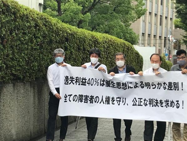 大阪地裁の前でデモを行う聴覚障害者団体の代表者らと井出さん(左から2人目)  (井出さん提供)