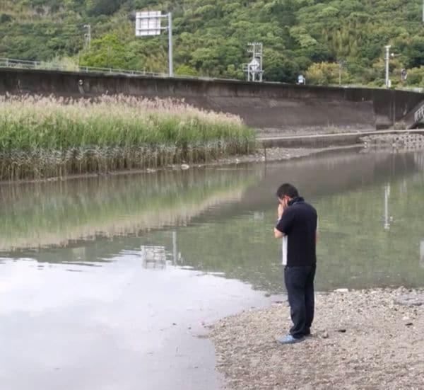 優空君が亡くなった下田川の現場で手を合わせる岡林さん(遺族提供)