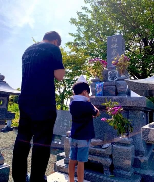 墓前で手を合わせる岡林さんと弟(遺族提供)