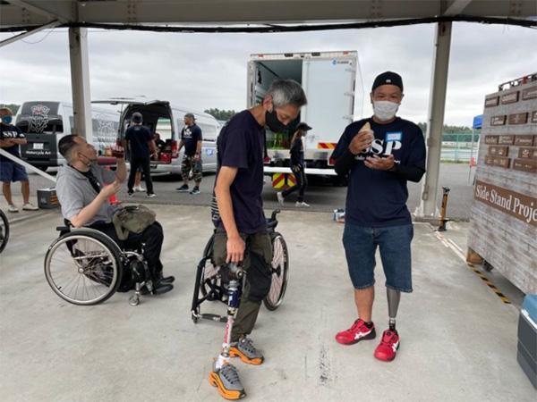 大腿部から義足を装着している丸野さん(中央)。右の男性も義足でサーキット走行に挑戦した(筆者撮影)