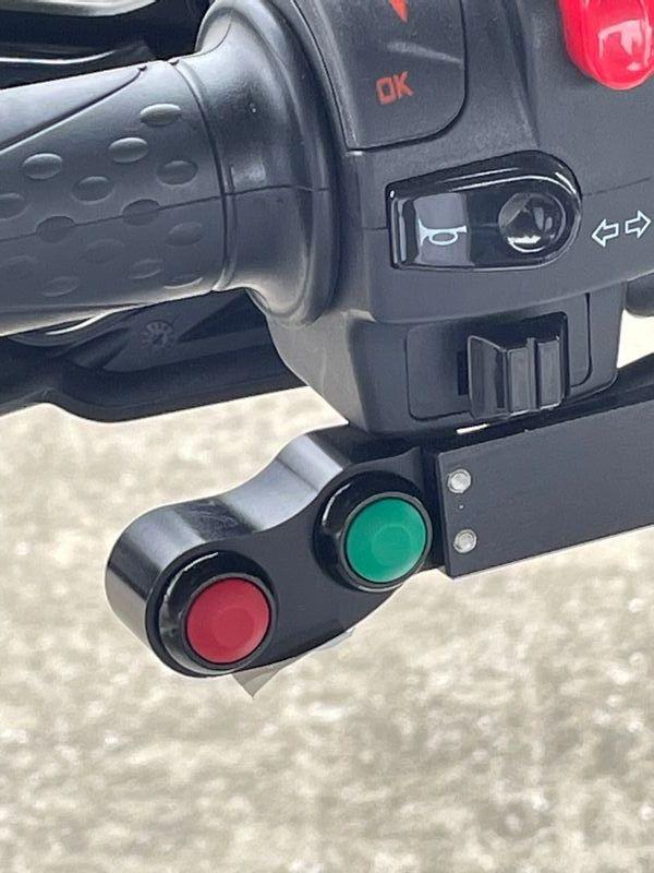 ギアチェンジはハンドルにつけられたスイッチを指で操作して行う。緑のボタンはシフトアップ、赤はシフトダウンだ(筆者撮影)