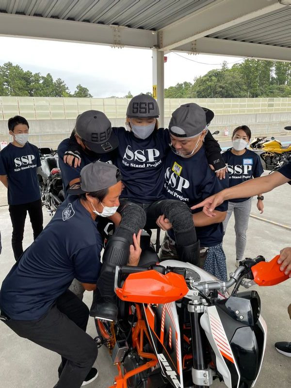 本番前、パラモトライダーをバイクに乗せる練習をするボランティアスタッフたち(筆者撮影)