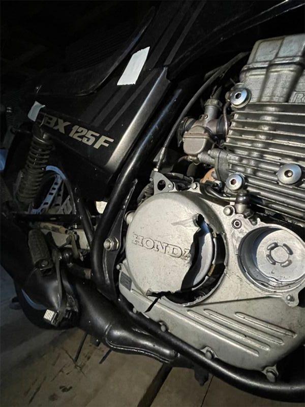 クランクケースカバーが破損している竹林さんのバイク。衝突の衝撃の大きさを物語る(筆者撮影)
